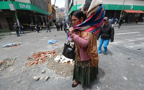 Some areas were blocked in the capital, La Paz, as police struggled to take control of the streets from protesters - Credit: Martin Alipaz/EPA-EFE/REX