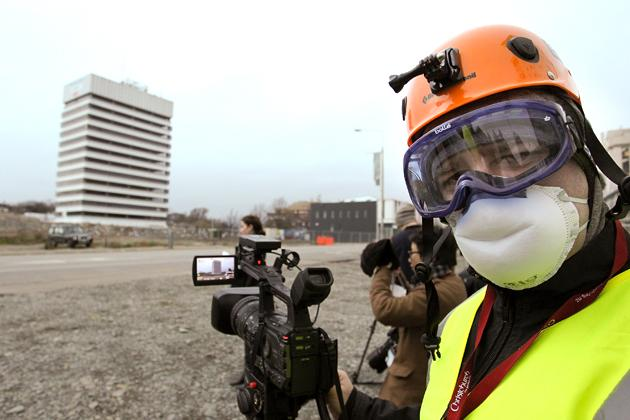 CHRISTCHURCH, NEW ZEALAND - AUGUST 05:  A cameraman prepares to film a controlled explosion on August 5, 2012 in Christchurch, New Zealand. The 14-story Radio Network House building in Worcester St, is the first of its kind in the city to be blown up in a controlled demolition since authorities began the massive task of bringing down the hundreds of quake-damaged buildings. The building was badly damaged in the magnitude-6.3 February 22, 2011 earthquake.  (Photo by Martin Hunter/Getty Images)