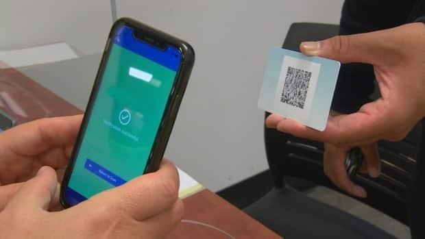 A student gets his proof of vaccination QR code scanned by a campus official at the University of Winnipeg. Just as COVID-19 vaccination policiesvary between Canadian post-secondary institutions, what's greeting students on the ground as they head in for their lectures and labs also differs by school. (CBC - image credit)