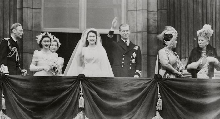 """Princess Elizabeth and Philip Mountbatten, Duke of Edinburgh, wave from a balcony at Buckingham Palace in London, shortly after their wedding on Nov. 20, 1947.<span class=""""copyright"""">Bettmann Archive/Getty Images</span>"""