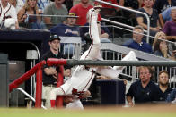 Atlanta Braves third baseman Josh Donaldson goes over the railing and into the camera well as he chases a foul ball by Washington Nationals' Juan Soto in the ninth inning of a baseball game Saturday, July 20, 2019, in Atlanta. Donaldson did not make the catch and Washington won 5-3. (AP Photo/John Bazemore)