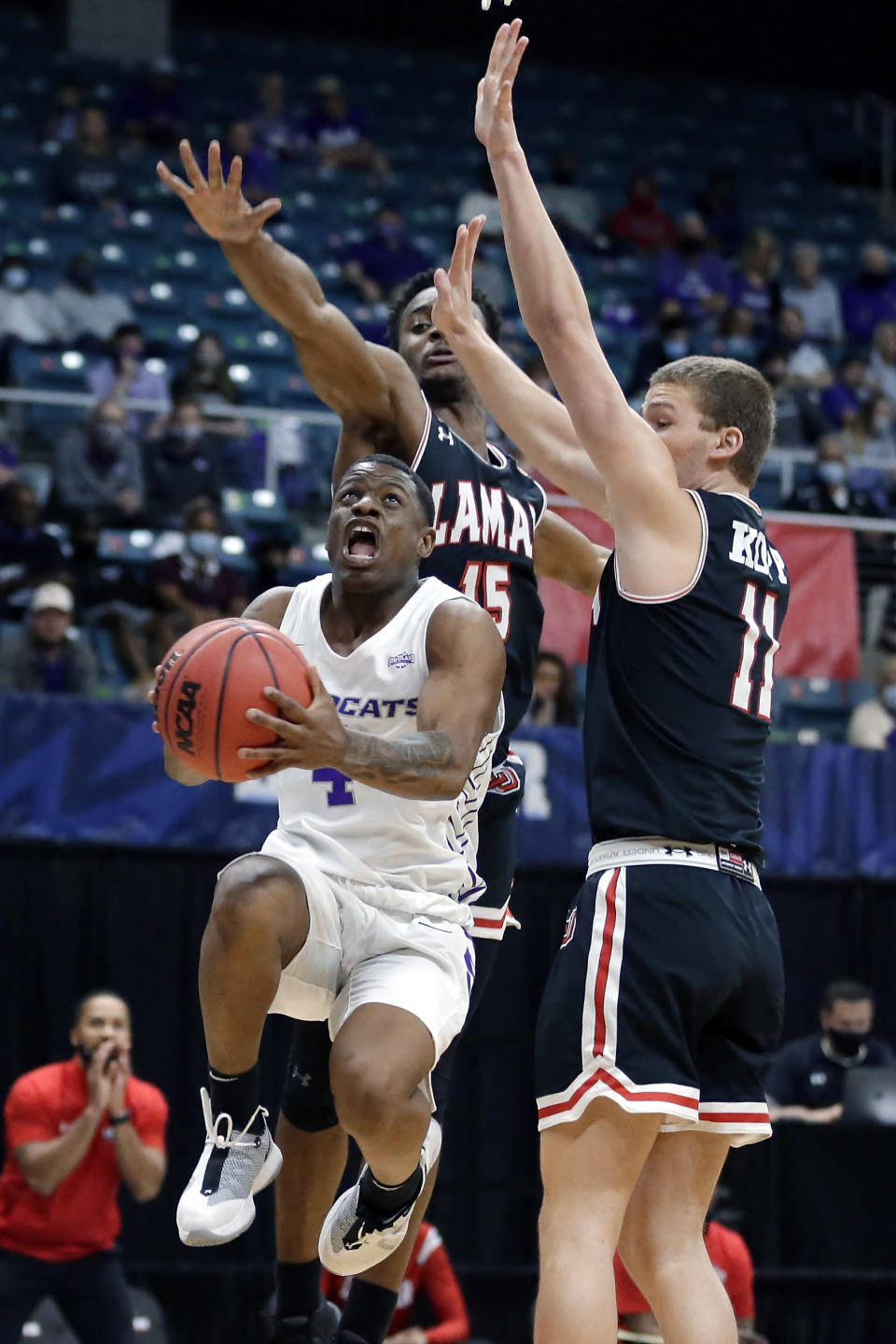 Abilene Christian guard Damien Daniels (4) shoots in front of Lamar forward Lincoln Smith (15) and guard Anderson Kopp (11) during the first half of an NCAA college basketball game in the Southland Conference semifinals Friday, March 12, 2021, in Katy, Texas. (AP Photo/Michael Wyke)