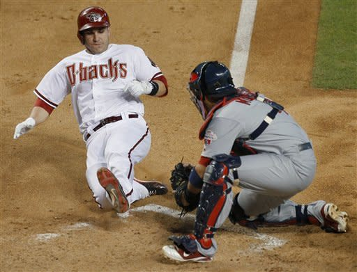 Arizona Diamondbacks' Miguel Montero, left, is tagged out at the plate by St. Louis Cardinals' Yadier Molina during the fourth inning of a baseball game Monday, May 7, 2012, in Phoenix. (AP Photo/Matt York)