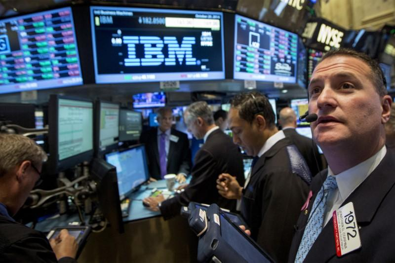 FILE PHOTO: Traders gather at the post that trades IBM on the floor of the New York Stock Exchange