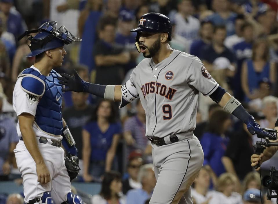 Houston Astros' Marwin Gonzalez celebrates in front of Los Angeles Dodgers catcher Austin Barnes after hitting a home run during the ninth inning of Game 2. (AP)