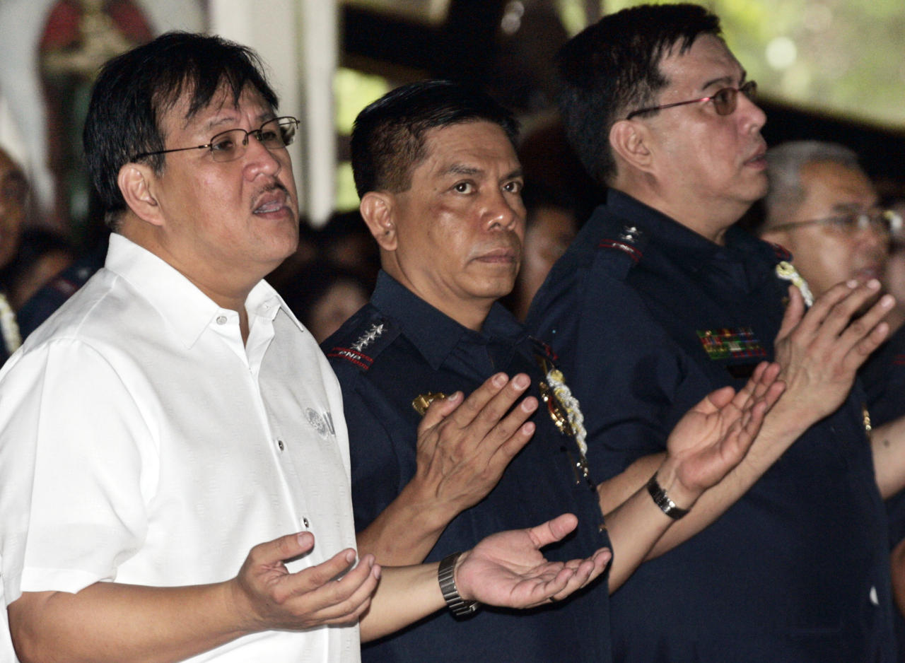 Department of Interior and Local Government Secretary Jessie Robredo, left, Philippine National Police Chief Director Gen. Raul Bacalzo, center, join other police officers and men during a mass for solidarity and unity Tuesday, Aug. 23, 2011 at the police headquarters in suburban Quezon City, north of Manila, Philippines. The police offered the mass commemorating the 1st anniversary of the Aug. 23 hijacking of a tourist bus where eight Hong Kong nationals were killed. (AP Photo/Pat Roque)