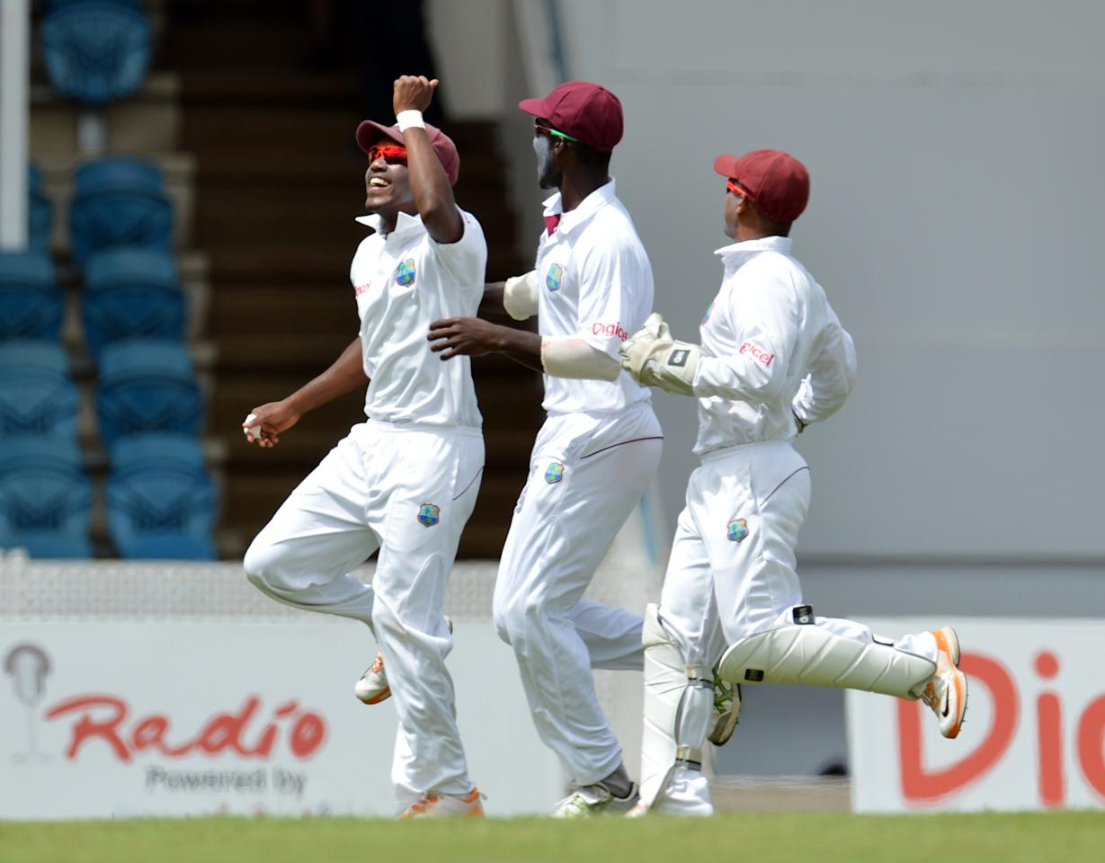 Darren Bravo (L) of the West Indies and teammates celebrate his catch of Australian batsman Matthew Wade during the second day of the second-of-three Test matches between Australia and West Indies April 16, 2012 at Queen's Park Oval in Port of Spain.     AFP PHOTO/Stan HONDA (Photo credit should read STAN HONDA/AFP/Getty Images)