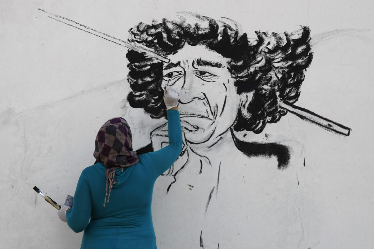 "A Libyan youth designs a graffiti depicting Moammar Gadhafi on a wall in Tripoli, Libya, Thursday, Sept. 8, 2011. The International Criminal Court is seeking Interpol's help in arresting ousted Libyan leader Moammar Gadhafi, the court's chief prosecutor said Thursday. Luis Moreno-Ocampo is asking the international police organization to issue a ""red notice"" for Gadhafi and says arresting him is a ""matter of time"". Gadhafi has not been seen in public for months. In an audio message broadcast Thursday by a pro-Gadhafi satellite TV channel based in Syria, he vowed never to leave Libya and called on supporters to keep fighting. (AP Photo/Francois Mori)"