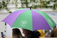 People shelter under an umbrella during a rain delay on day one of the Wimbledon Tennis Championships in London, Monday June 28, 2021. (AP Photo/Kirsty Wigglesworth)