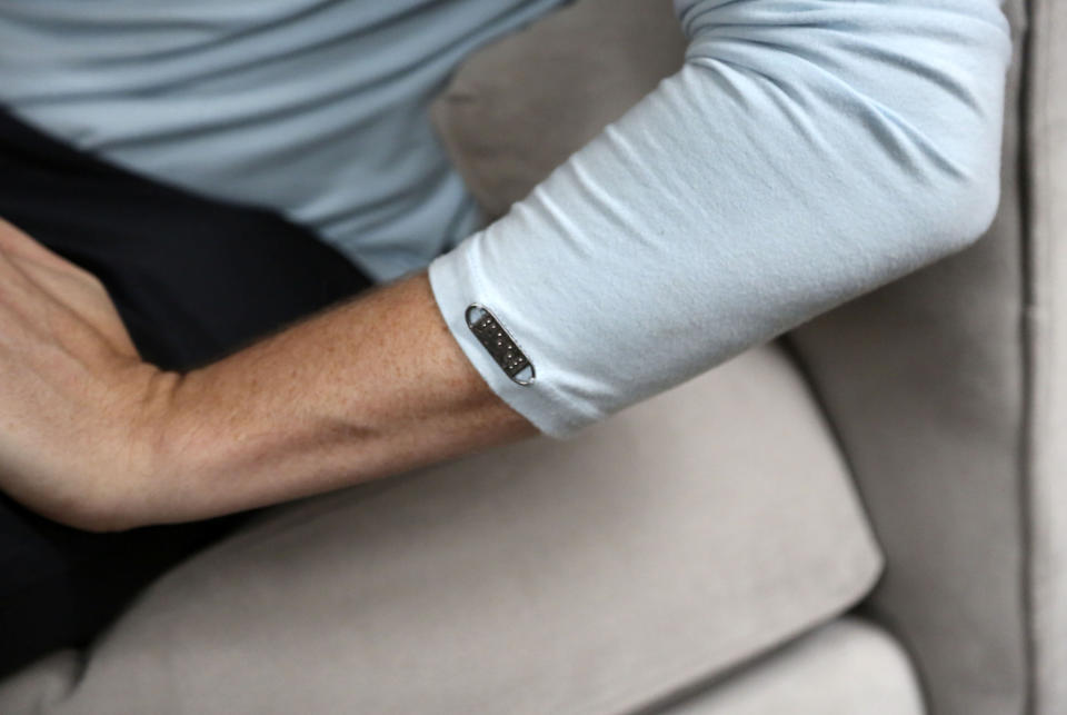 """A metal tag reading """"feel"""" in braille is stitched to the left arm of Bradford Manning's long sleeve shirt produced by their company Two Blind Brothers, in New York City on Friday, Oct. 23, 2020. The brothers have raised more than $700,000, which they've donated to preclinical research trials to help cure blindness. (AP Photo/Jessie Wardarski)"""