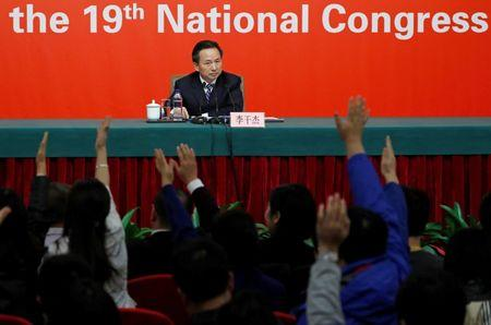 Reporters raise their hands to ask a question during a news conference with Chinese Minister of Environmental Protection Li Ganjie at the 19th National Congress of the Communist Party of China in Beijing, China October 23, 2017. REUTERS/Tyrone Siu