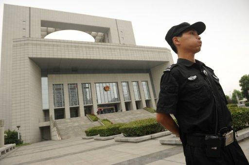 Police stand guard outside the Intermediate People's Court in Hefei during the murder trial of Gu Kailai, wife of the disgraced leader Bo Xilai, in August 2012. Gu was convicted of Neil Heywood's murder and given a suspended death sentence