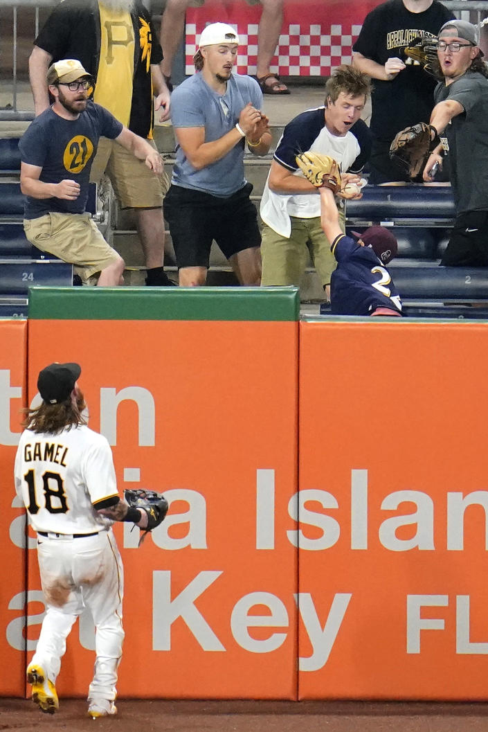 Pittsburgh Pirates left fielder Ben Gamel (18) looks up as a fan makes the catch in the left field stands of a three-run home run hit by Milwaukee Brewers' Manny Pina during the sixth inning of a baseball game in Pittsburgh, Thursday, July 29, 2021. (AP Photo/Gene J. Puskar)
