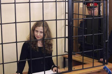 Alyokhina, jailed member of Russian punk band Pussy Riot, looks out from a defendants' box as she attends a court hearing in Nizhny Novgorod