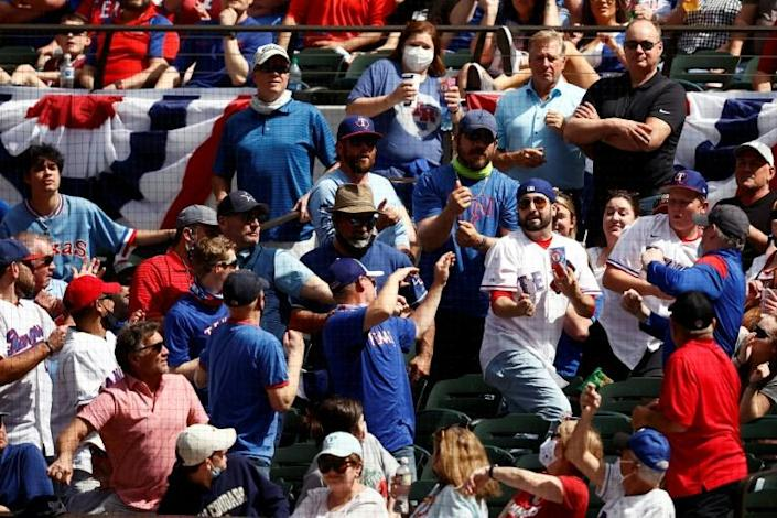Fans battle for a foul ball at the Texas Rangers' home opener against the Toronto Blue Jays on Monday