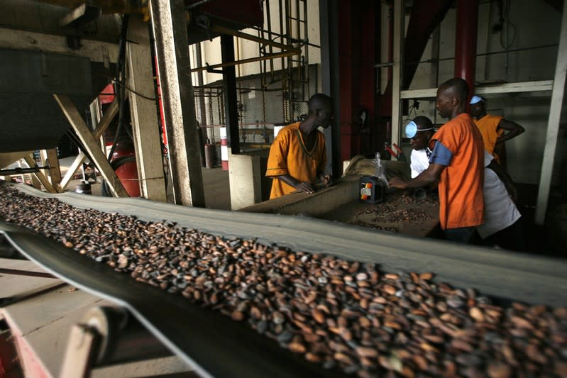 Workers handle cocoa beans at a Barry Callebaut cocoa factory in San Pedro