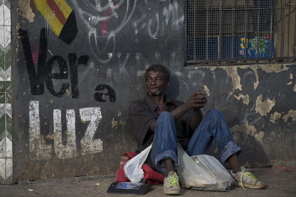 """A man sits on the street in """"Cracolandia"""" (Crackland), in downtown Sao Paulo, Brazil on January 15, 2014. AFP PHOTO/Nelson ALMEIDA        (Photo credit should read NELSON ALMEIDA/AFP via Getty Images)"""