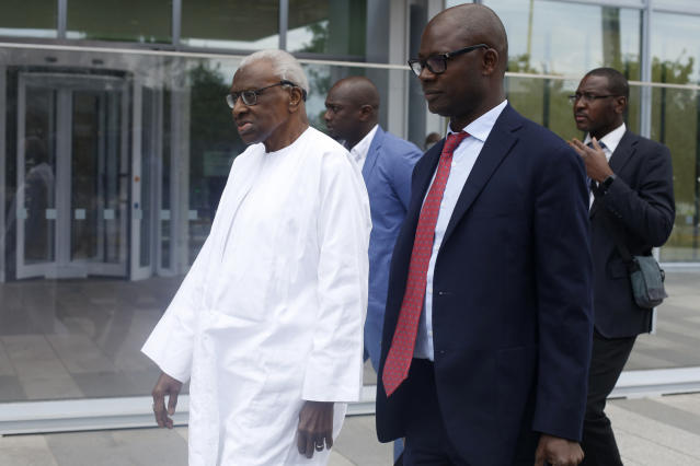 Former president of the IAAF (International Association of Athletics Federations) Lamine Diack, left, arrives at the Paris courthouse, Wednesday, June 10, 2020. A sweeping sports corruption trial opened Monday in Paris involving allegations of a massive doping cover-up that reached to the top of world track and field's governing body. Lamine Diack, 87, who served as president of the body for nearly 16 years, is among those accused of receiving money from Russian athletes to hide their suspected doping so they could compete at the Olympics in 2012 and other competitions. (AP Photo/Thibault Camus)