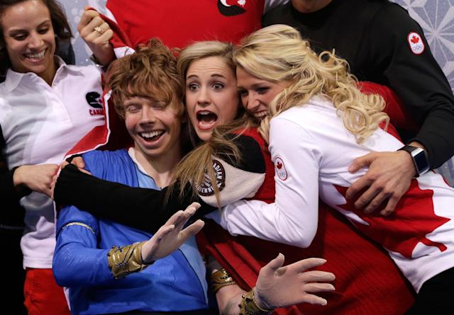 SOCHI, RUSSIA - FEBRUARY 09: Kevin Reynolds of Canada reacts with teammates and coaches after receiving his score in the Men's Figure Skating Men's Free Skate during day one of the Sochi 2014 Winter Olympics at Iceberg Skating Palace onon February 9, 2014 in Sochi, Russia. (Photo by Darren Cummings/Pool/Getty Images)