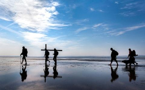 Pilgrims carry crosses to the Holy Island of Lindisfarne in Northumberland during the annual Christian Easter pilgrimage - Credit: Danny Lawson/PA Wire