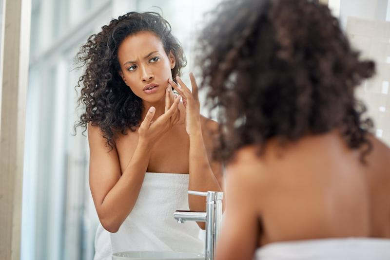 .Shot of an attractive young woman inspecting her face in the bathroom mirror