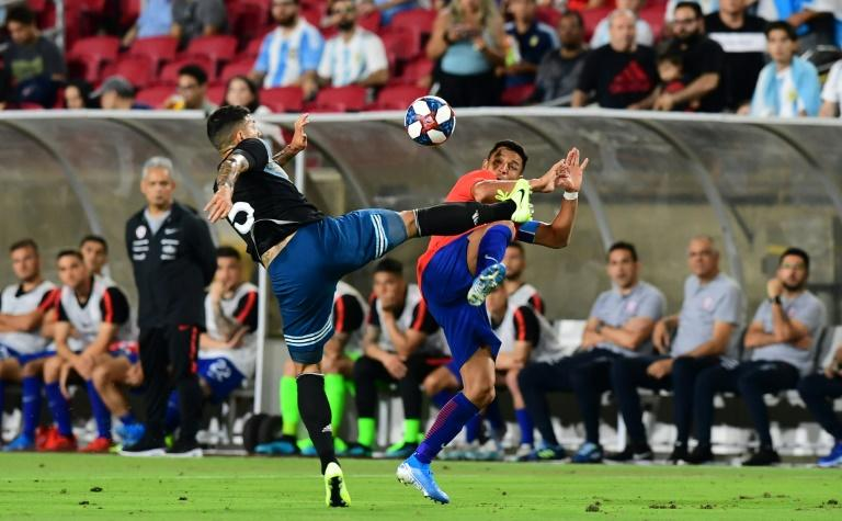 Leandro Paredes of Argentina (L) vies for the ball with Alexis Sanchez of Chile (R) as the teams played to a 0-0 draw in their friendly international football match at LA Memorial Coliseum