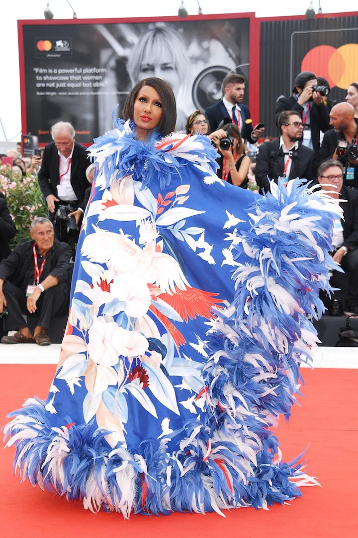 Setting the fashion bar high for fellow attendees, Iman chose a feathered Valentino cape for the grand opening ceremony. <em>[Photo: Getty]</em>