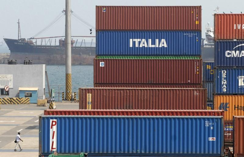 A worker walks near containers stacked at the Chennai port