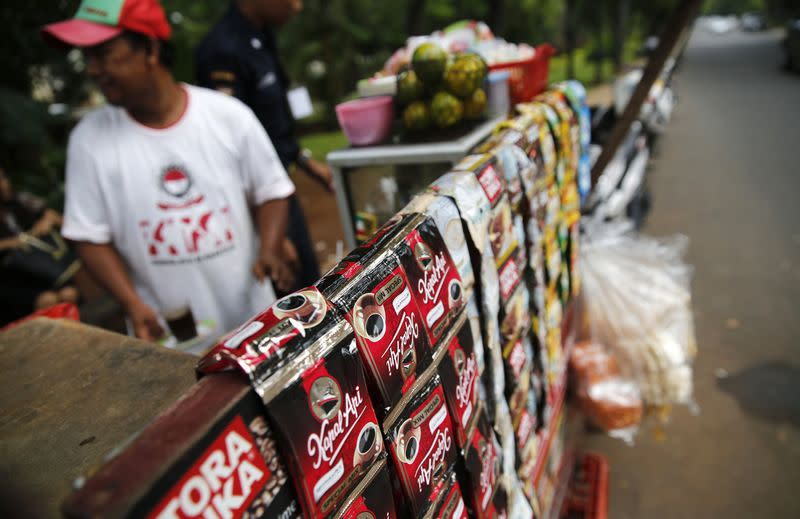 A vendor sells drinks using packets of instant coffee from a stall on a street in central Jakarta