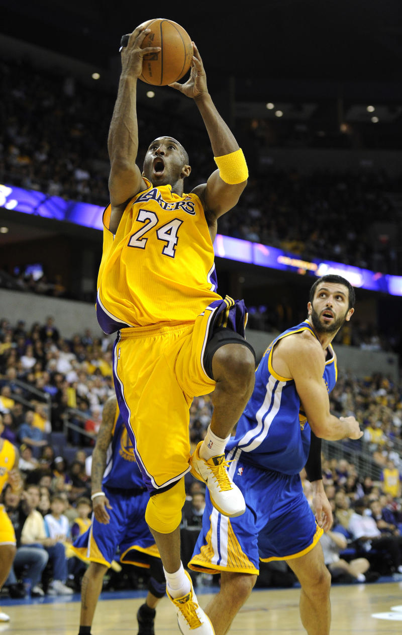 Los Angeles Lakers shooting guard Kobe Bryant, left, goes up for a shot as Golden State Warriors small forward Vladimir Radmanovic of Serbia looks on during the second half of their NBA basketball game, Friday, Oct. 22, 2010, in Ontario, Calif. (AP Photo/Mark J. Terrill)