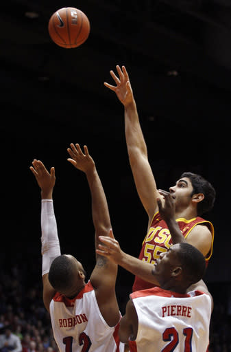 Southern California's Omar Oraby (55) shoots over Dayton's Jalen Robinson (12) and Dyshawn Pierre (21) during the first half of an NCAA college basketball game, Sunday, Dec. 22, 2013, in Dayton, Ohio. (AP Photo/Skip Peterson)