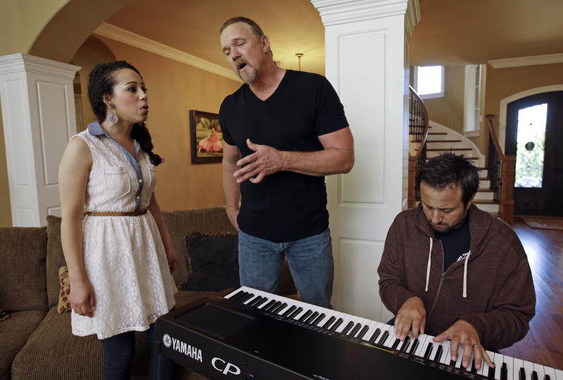 "In this May 13, 2013 photo, country singer Trace Adkins, center, and Maureen Maltez rehearse the song ""Watch the World End"" in Franklin, Tenn. Atkins recently heard Maltez sing at a junior college fundraiser, and asked her to sing with him at some upcoming appearances in New York. Playing the keyboards is Jon Coleman. (AP Photo/Mark Humphrey)"