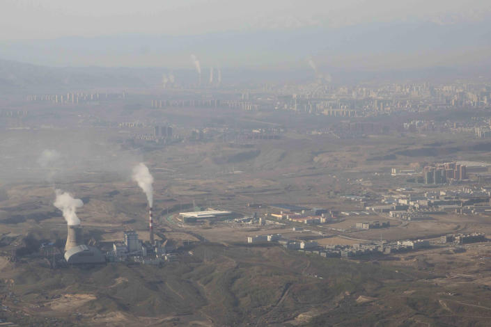 """FILE - In this Wednesday, April 21, 2021 file photo, smoke and steam rise from towers at the coal-fired Urumqi Thermal Power Plant in Urumqi in western China's Xinjiang Uyghur Autonomous Region. A report released on Wednesday, Sept. 15, 2021 by Climate Action Tracker says only one nation, tiny The Gambia in Africa, has plans in line with limiting warming to the agreed upon goal set by the 2015 Paris agreement. Top carbon emitting nation China and third highest carbon polluting nation India are what the report calls """"highly insufficient"""" or more in line with 4 degrees Celsius (7.2 degrees Fahrenheit) of warming since pre-industrial times. (AP Photo/Mark Schiefelbein)"""