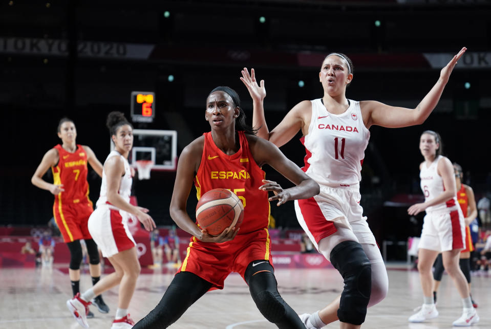 Spain's Astou Ndour (45), center, holds the ball as Canada's Natalie Achonwa (11) questions the foul call during women's basketball preliminary round game at the 2020 Summer Olympics, Sunday, Aug. 1, 2021, in Saitama, Japan. (AP Photo/Charlie Neibergall)