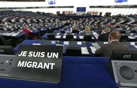 "A leaflet with the slogan ""I am a migrant"" is placed on the desk of a MEP during a debate on the latest tragedies in the Mediterranean and EU migration and asylum policies at the European Parliament in Strasbourg"