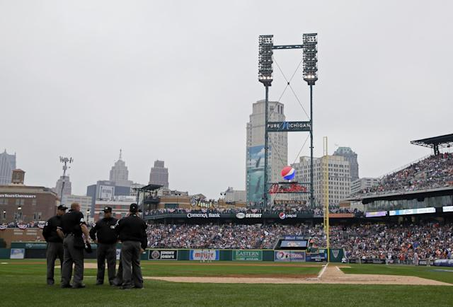 Umpires gather and wait as stadium lights go out at Comerica Park to delay the game in the second inning during Game 3 of the American League baseball championship series between the Boston Red Sox and the Detroit Tigers Tuesday, Oct. 15, 2013, in Detroit. (AP Photo/Matt Slocum)