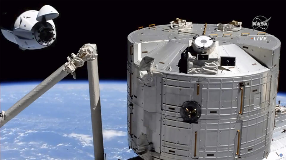 In this image made from NASA TV, the SpaceX Crew Dragon spacecraft, left, approaches to the international space station, Saturday, April 24, 2021. The recycled SpaceX capsule carrying four astronauts has arrived at the International Space Station, a day after launching from Florida. (NASA via AP)