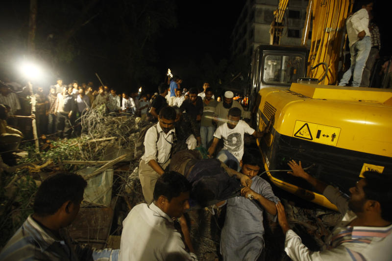 Rescue workers carry the body of a women near the site of a residential building collapsed in Thane, Mumbai, India, Thursday, April 4, 2013. At least 6 persons were killed and 40 were injured when an under construction residential building collapsed on Thursday evening according to local reports.(AP Photo/Rafiq Maqbool)