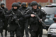 Police in tactical gear conduct a search for a suspect in the Boston Marathon bombings, Friday, April 19, 2013, in Watertown, Mass. The bombs that blew up seconds apart near the finish line of the Boston Marathon left the streets spattered with blood and glass, and gaping questions of who chose to attack and why. (AP Photo/Matt Rourke)