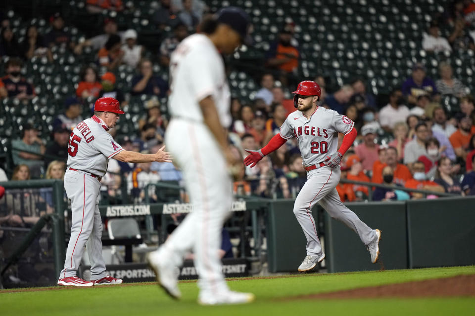 Los Angeles Angels' Jared Walsh (20) celebrates with third base coach Brian Butterfield (55) after hitting a home run off Houston Astros starting pitcher Luis Garcia, center, during the sixth inning of a baseball game Monday, May 10, 2021, in Houston. (AP Photo/David J. Phillip)