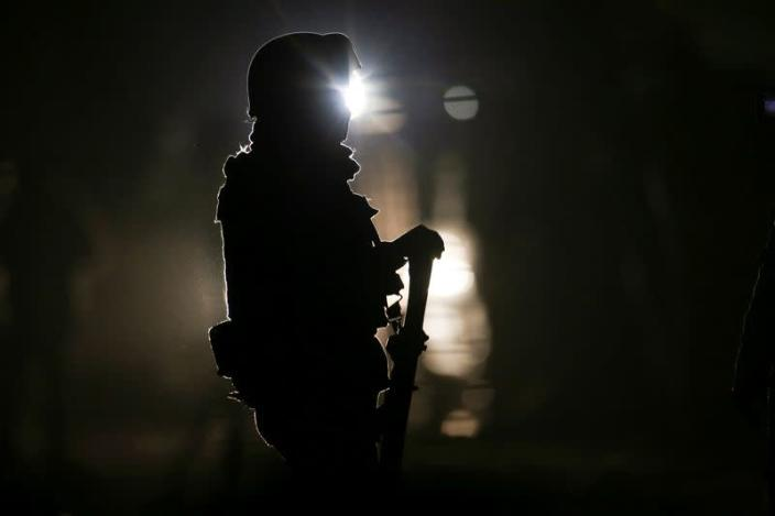 A soldier guards the area where eleven people were killed when unidentified gunmen riding in a truck opened fire in Tonala