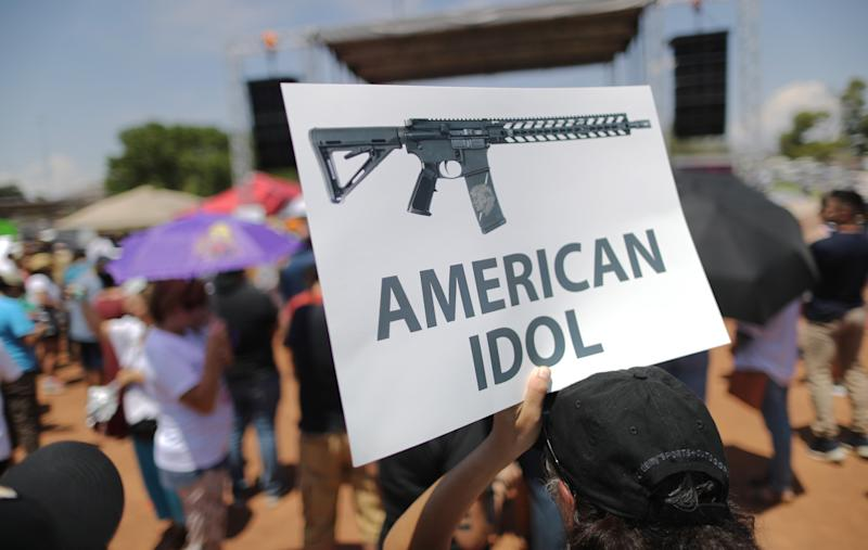 A demonstrator holds a sign depicting an assault rifle at a protest against President Trump's visit, following a mass shooting which left at least 22 people dead, on Aug. 7, 2019 in El Paso, Texas. (Photo: Mario Tama/Getty Images)