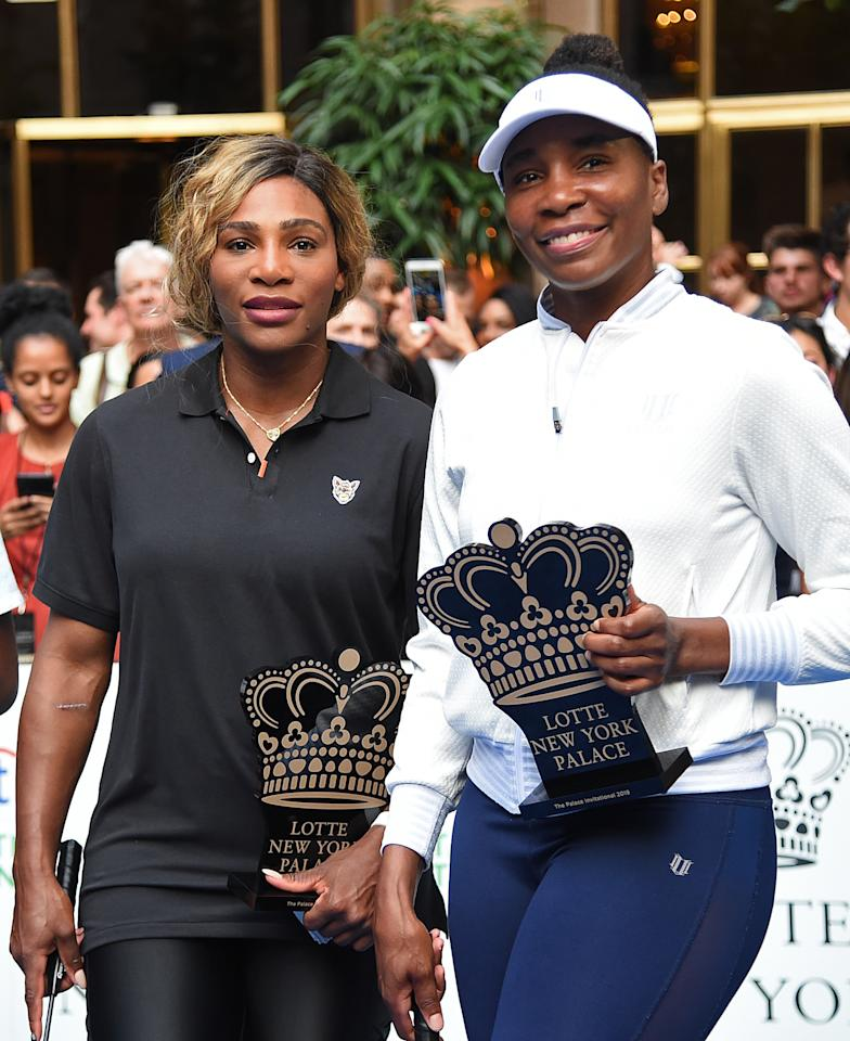 The Williams sisters posed with the trophies after defeating Coco Gauff and Rafael Nadal in their badminton game.