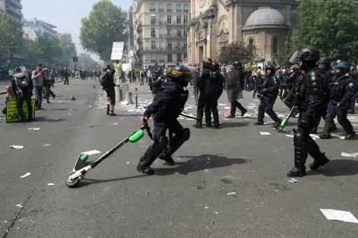 A French riot police officer removed an electric scooter that was used as a weapon by protesters at this year's May Day rally in Paris