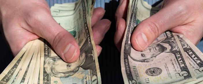 Man's hands holding out piles of cash in American five and twenty dollar bills