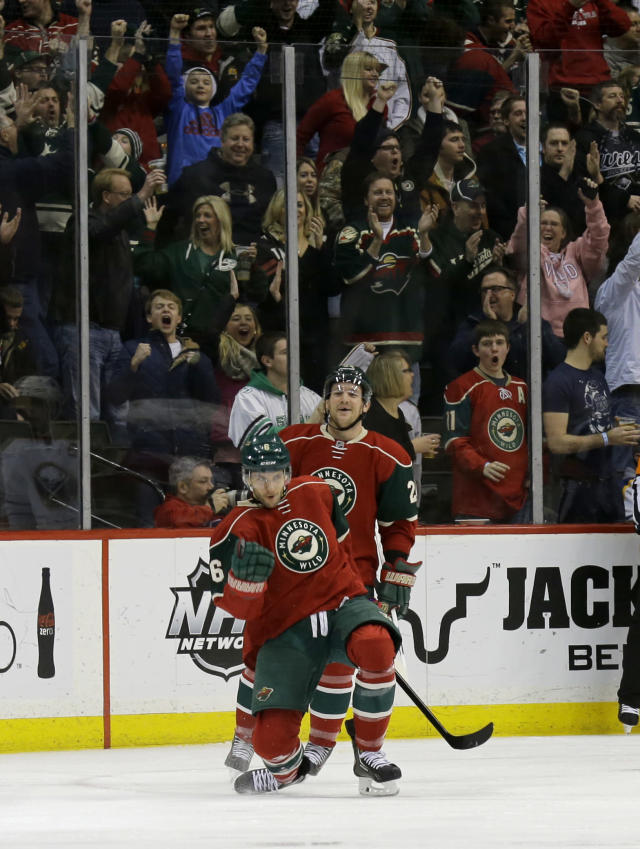 Minnesota Wild defenseman Marco Scandella, front, celebrates his goal as Wild left wing Matt Cooke, rear, comes to congratulate him and fans cheer during the second period of an NHL hockey game in St. Paul, Minn., Thursday, Jan. 2, 2014. (AP Photo/Ann Heisenfelt)
