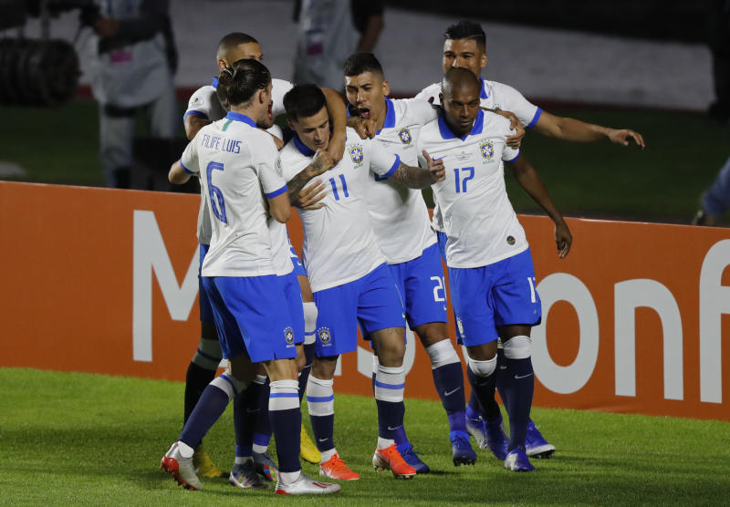 Brazil's Philippe Coutinho, center, celebrates scoring his side's opening goal with teammates during a Copa America Group A soccer match at the Morumbi stadium in Sao Paulo, Brazil, Friday, June 14, 2019. (AP Photo/Nelson Antoine)