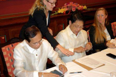 Philippine government negotiators Jesus Dureza (L) and Silvestre Bello sign an indefinite ceasefire agreement with communist rebels at a meeting in Oslo, Norway, August 26, 2016. REUTERS/Alister Doyle
