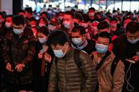 Passengers wearing face masks walk to their train at the main railway station in Wuhan, China