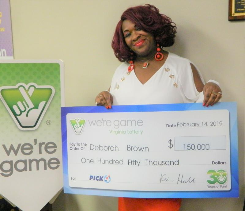 "This Feb. 14, 2019 photo provided by Virginia Lottery shows Debrorah Brown holding up a check after winning the Pick 4 in Richmond, Va.  Brown says she purchased 20 Pick 4 tickets with the numbers 1-0-3-1 after seeing those numbers ""a couple of times during the day."" She then bought 10 more because she was really feeling it. The number combination won the Feb. 11 drawing and each ticket was worth $5,000. (Virginia Lottery via AP)"